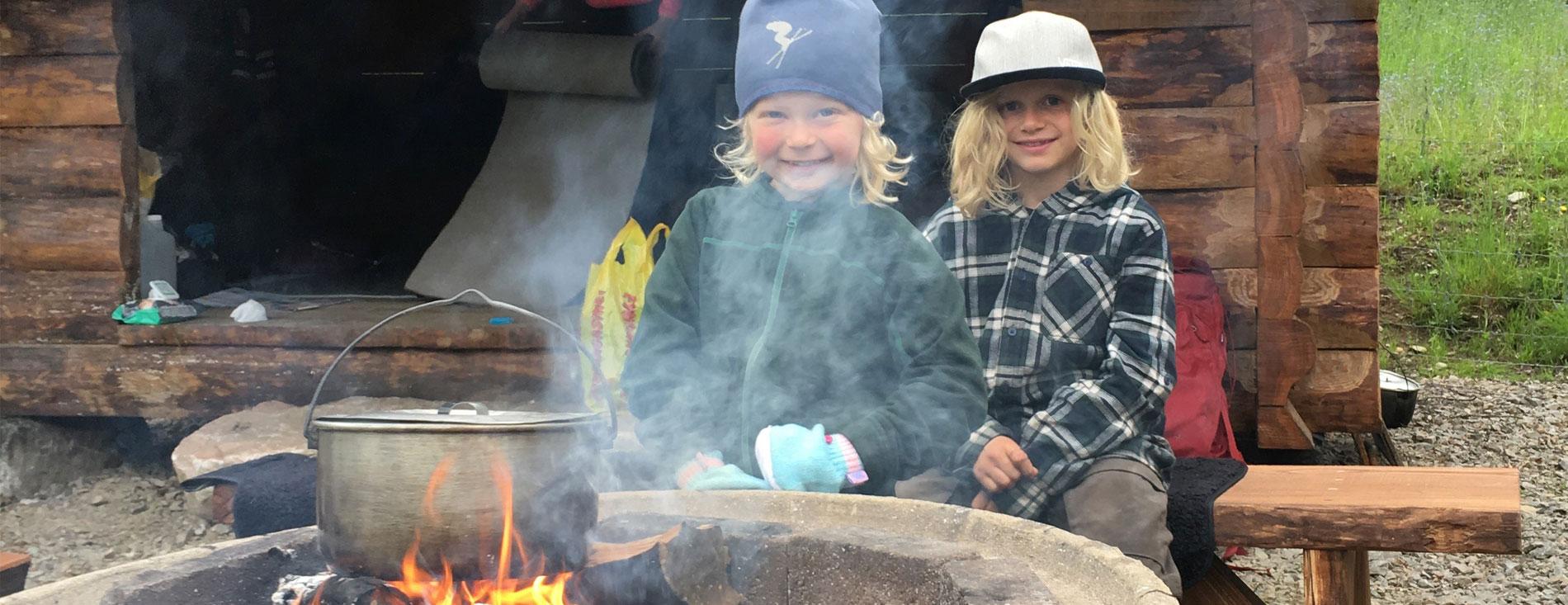 Barn vid eld framför vindskydd på Kungslederna